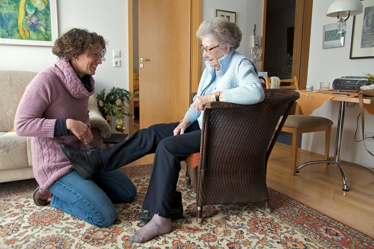caretaker helping elderly women in her home providing caring senior care