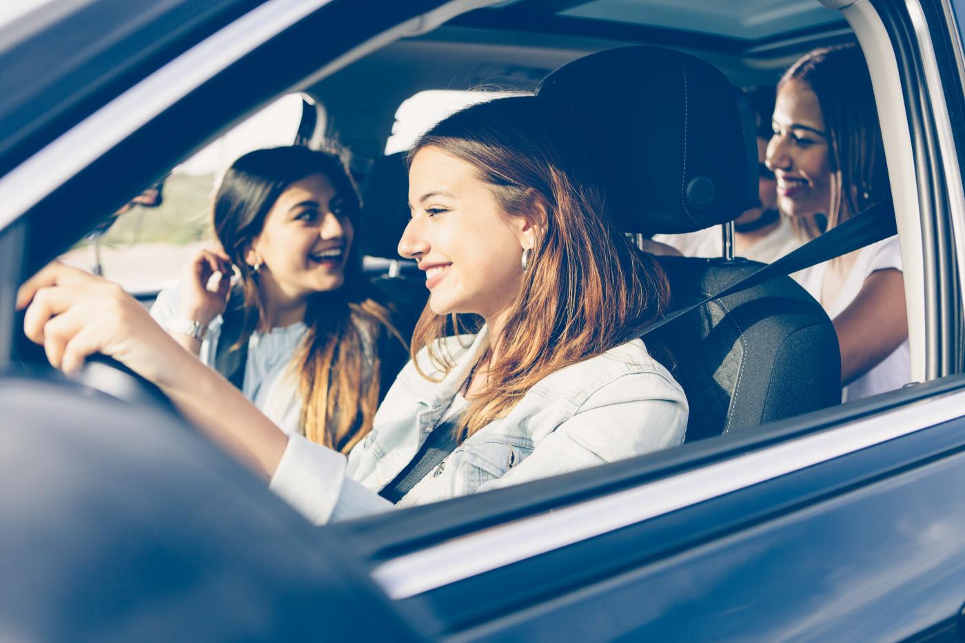 teenagers in car smiling