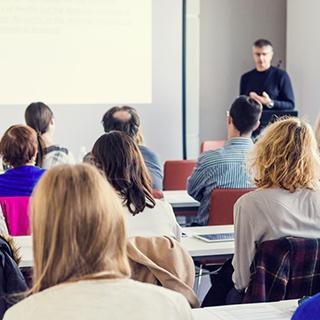 Foto de uma sala de aula, tirada do fundo, com 7 alunos já adultos e um professor na frente da lousa branca.