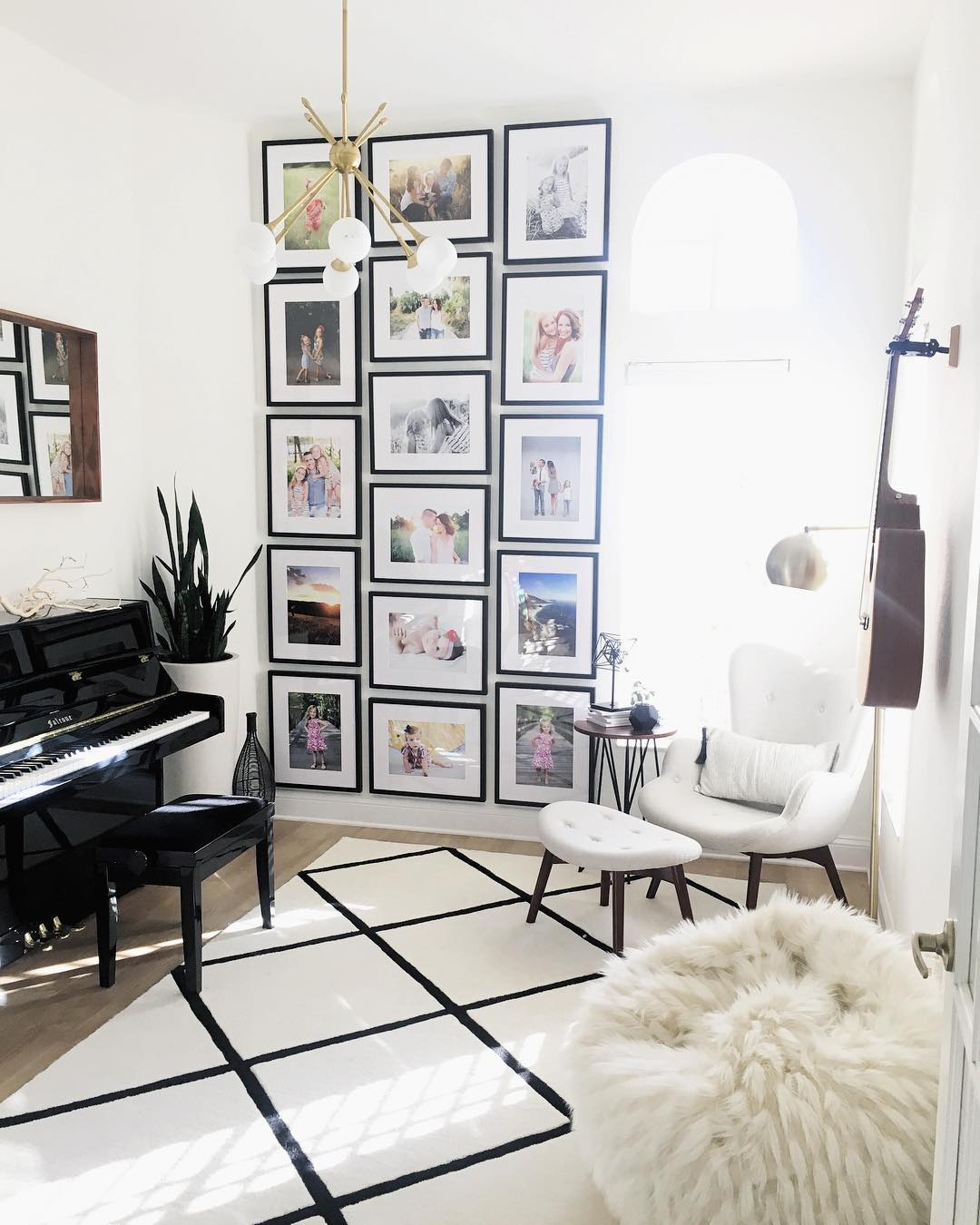 gallery wall of family photos in black frames in living room with piano and bean bag chairs