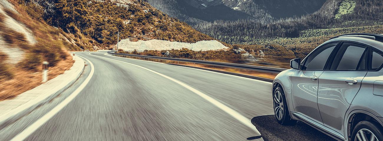 auto plateado rodando sobre la carretera frente a las montañas