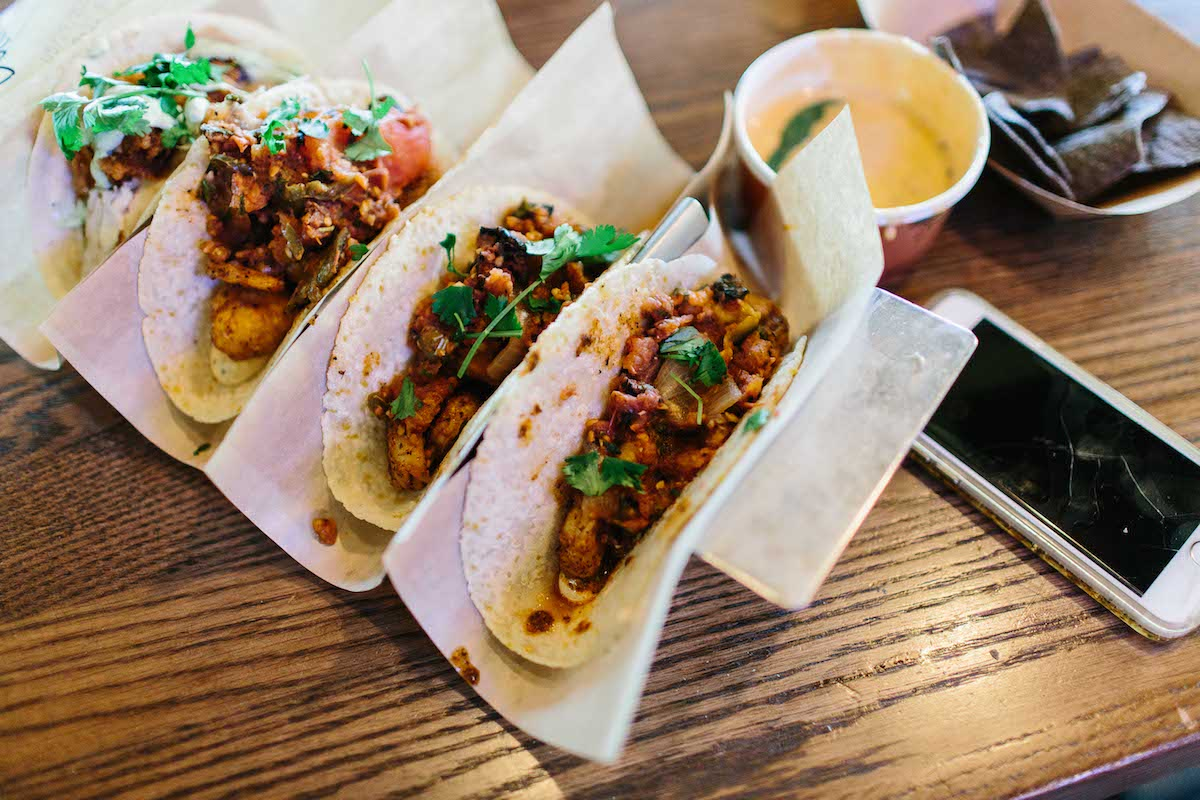 Four delicious tacos await consumption in their holder