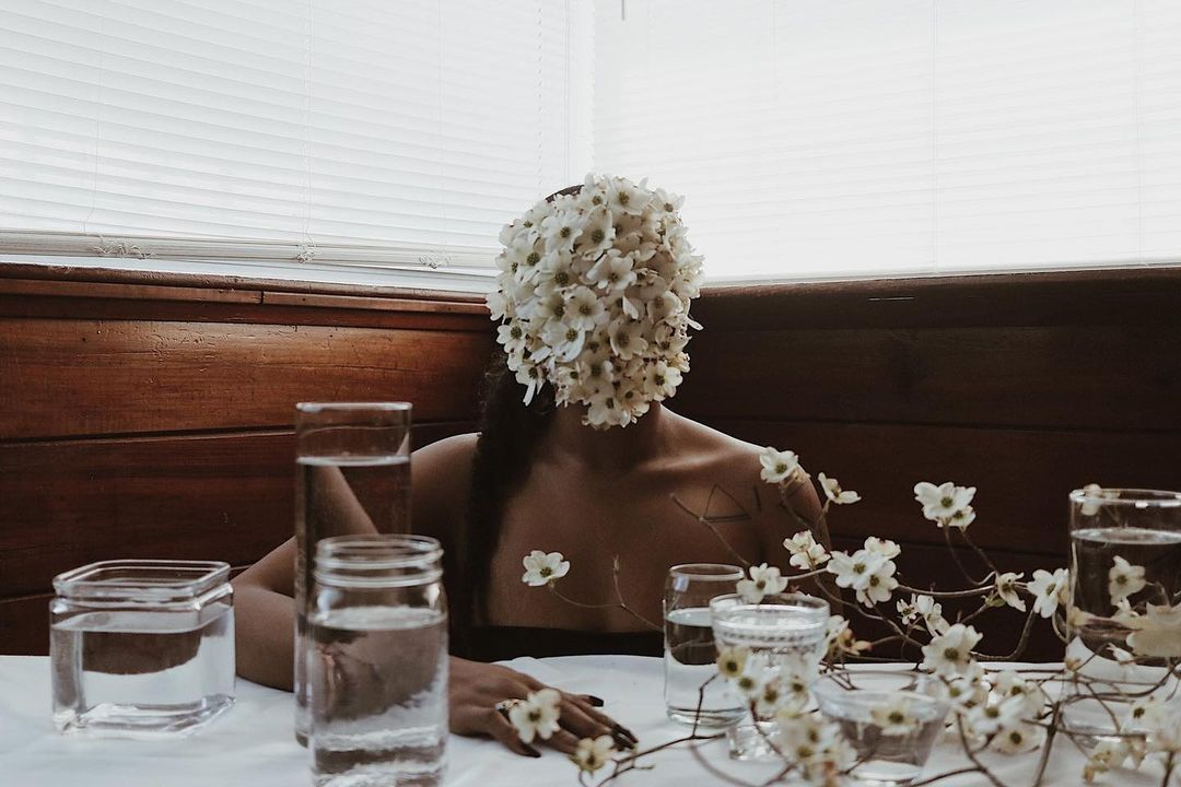 woman at dining table with flowers on her face