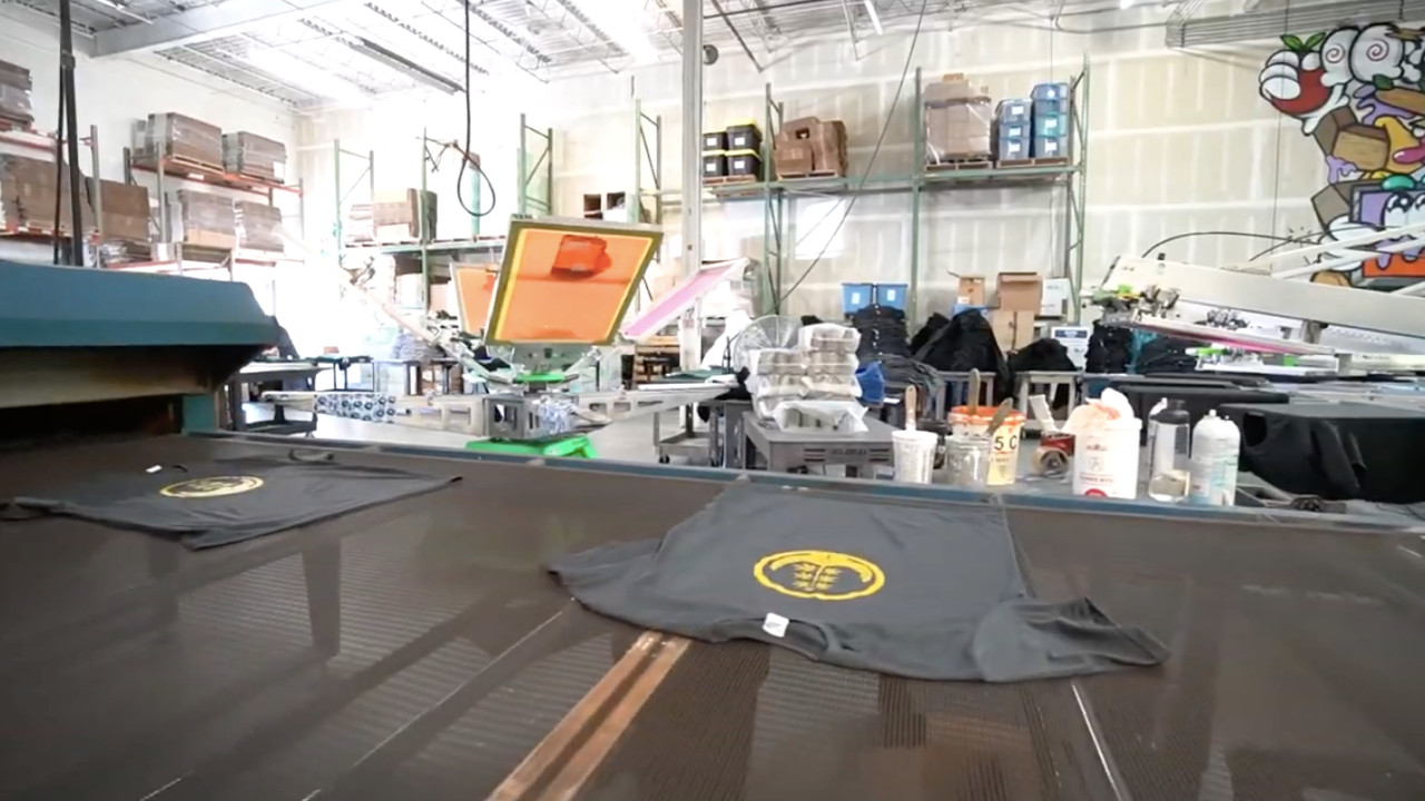 Cannabis merchandise rolling off a screen printing production line (t-shirts)