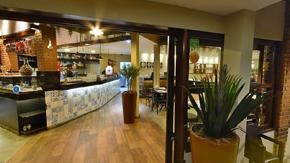 Foto da entrada de uma pizzaria, da parte interna. Tem colunas de madeira, um piso claro e uma luz bem aconchegante.