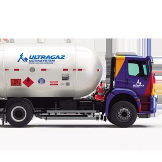 Foto de caminhão da Ultragaz de lado, nas cores azul, vermelha e amarela com o baú cilíndrico na cor branca com logo do Ultrasystem estampado.