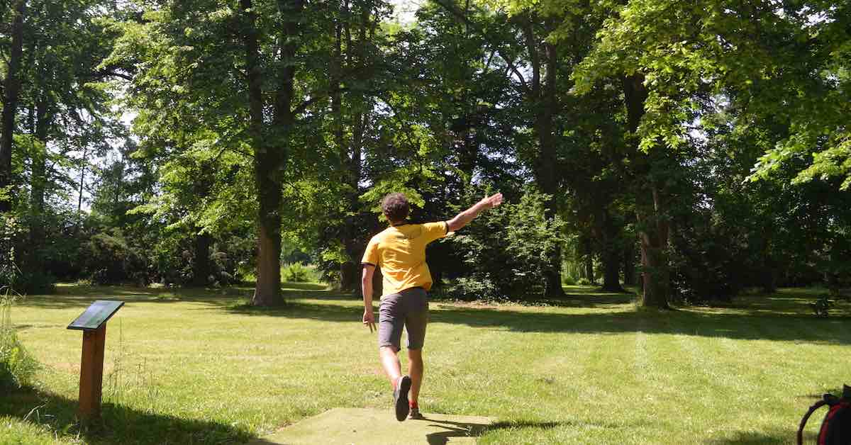 A player in a yellow shirt and shorts throws on a disc golf hole in a park setting with grass and many trees