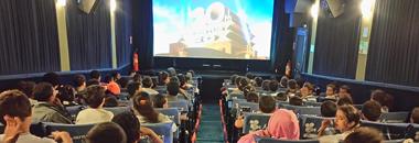 Foto tirada do fundo de um auditório com vários alunos assistindo um filme.o