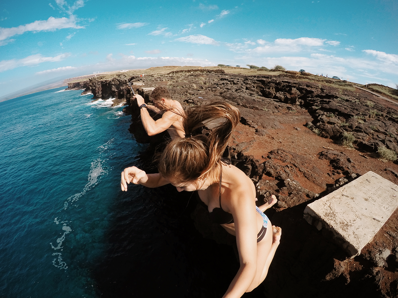 A couple jumping off cliff into water
