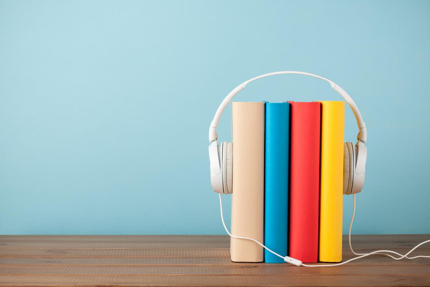 four books with headphones around them