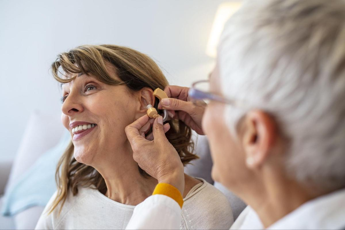 EPIC Hearing: Doctor putting a hearing aid on a female patient's ear