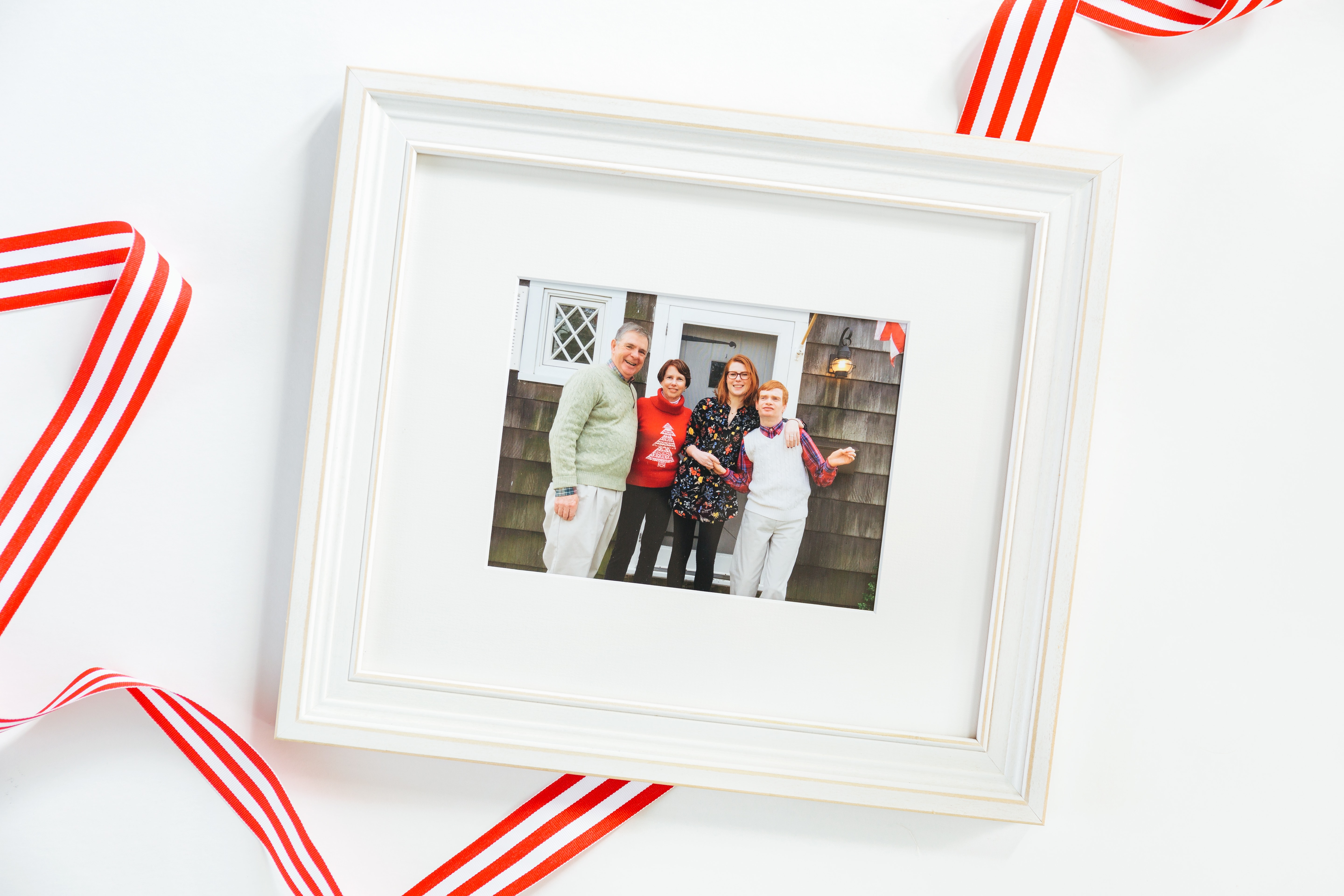 framed photo of a family during Christmas in while frame with red ribbon