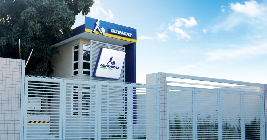 Foto da fachada de uma revenda da Ultragaz com paredes nas cores brancas e testeira com logo escrito. Ao fundo um céu azul e algumas árvores verdes.