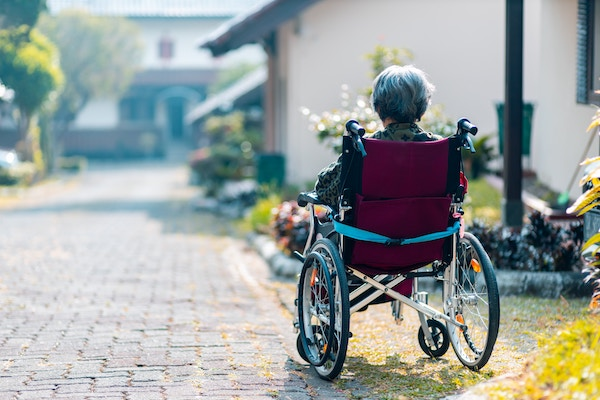 woman in wheelchair with Alzheimer's - a type of dementia affecting memory, thinking, and behavior