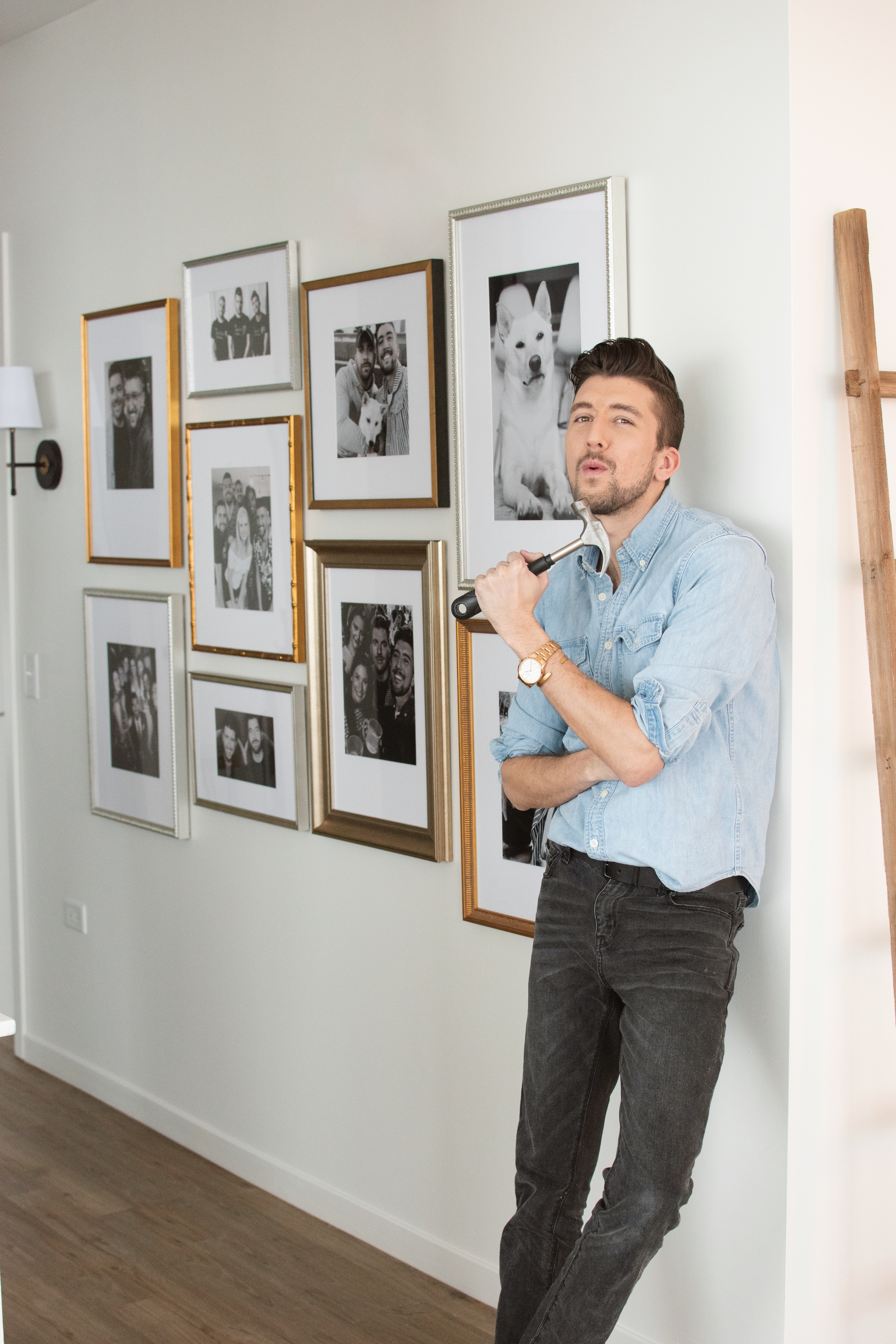 man with hammer in front of gallery wall