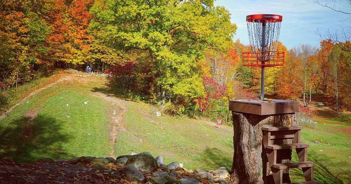 A red disc golf basket elevated on a tall stump in foreground with a background of a hill and trees in fall colors