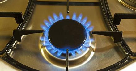 Foto da boca de um fogão acesa com a chama azul.