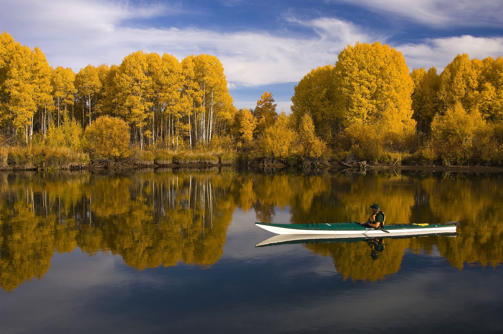 A kayaker rests in an autumn lake.