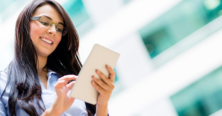 Foto de uma mulher de cabelo moreno sorrindo  ao mexer no tablet.