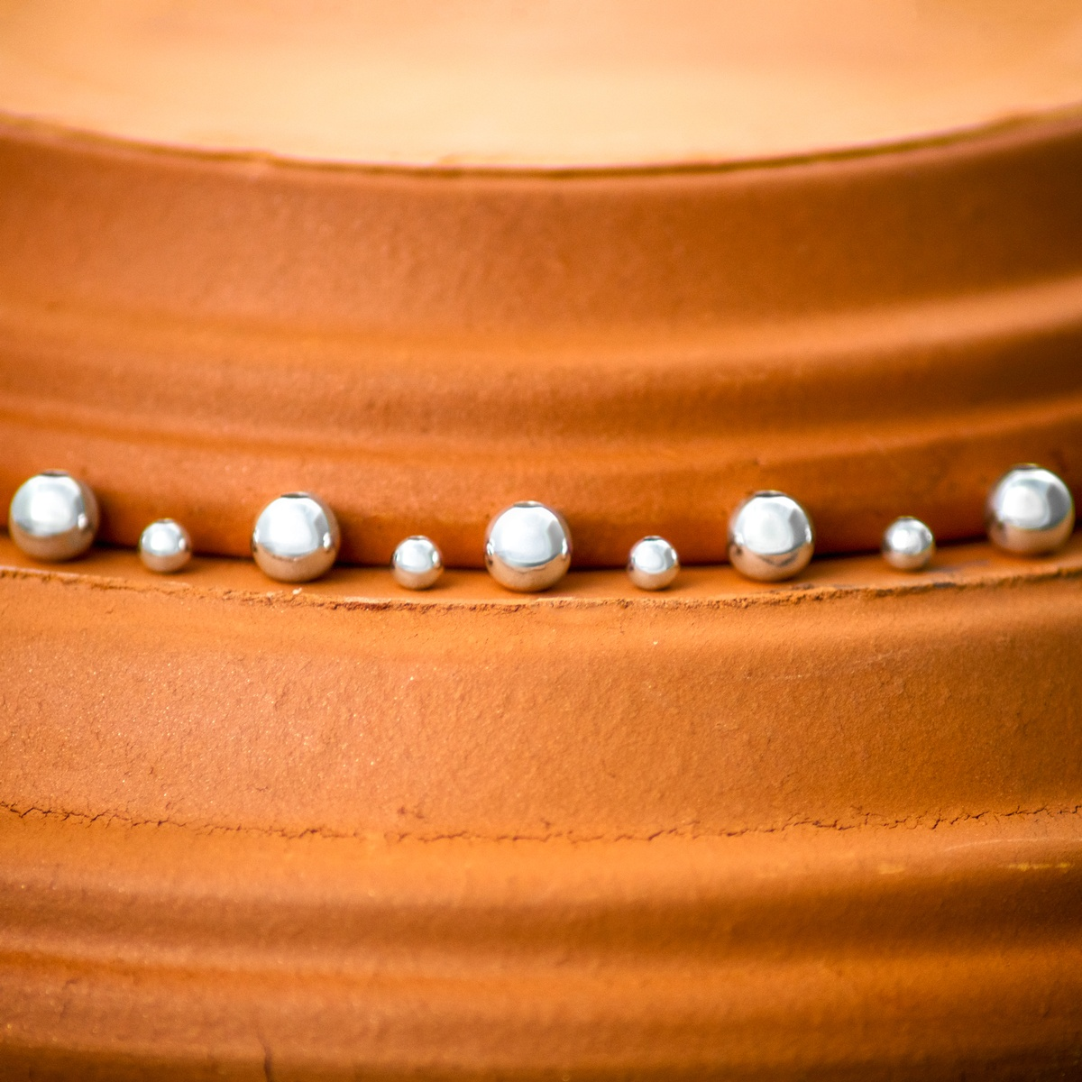 Sterling Silver beads that have been slightly desaturated on terra-cotta pot