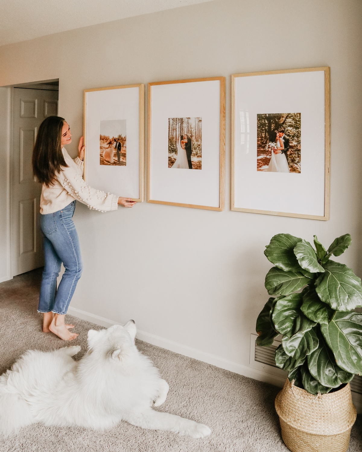 woman hanging wood triptych frames with dog at her feet