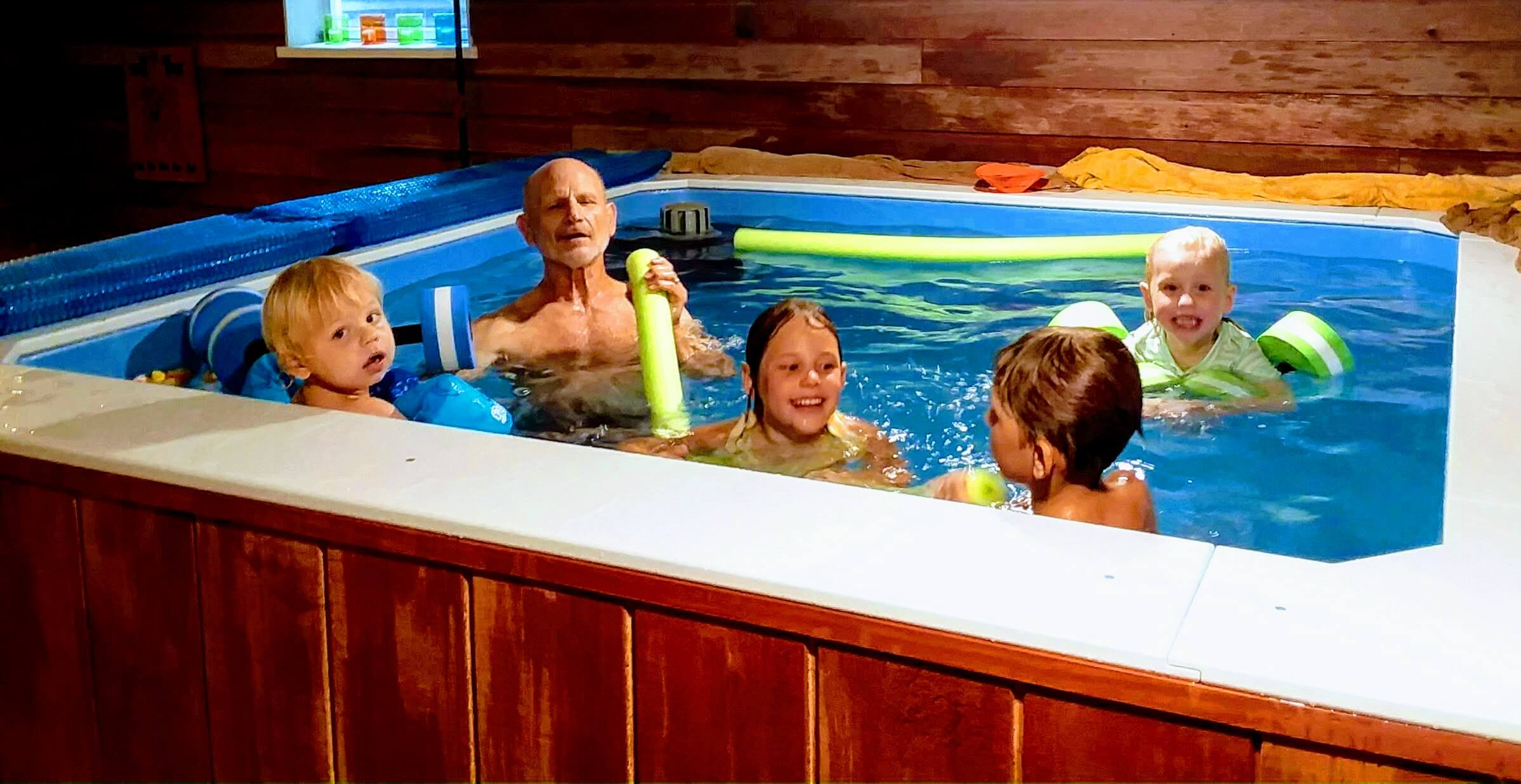Joan's husband and their grandkids enjoy playtime in her Endless Pools WaterWell therapy pool