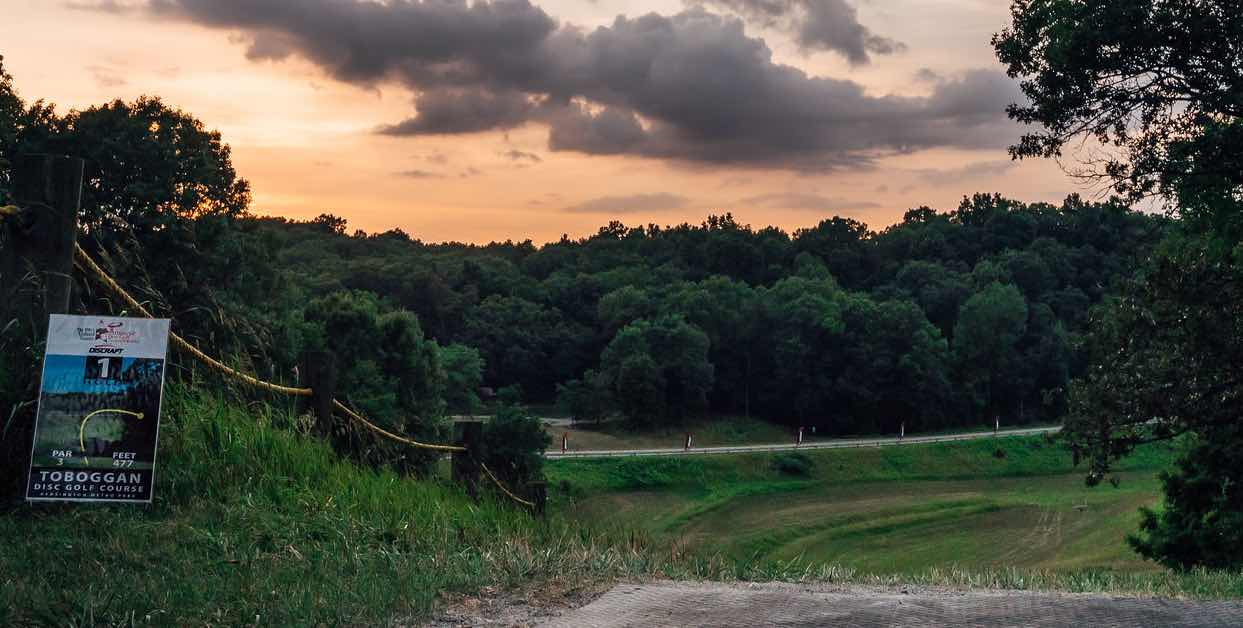 View from a disc golf teeing area high up on a hill overlooking a steep drop at sunrise