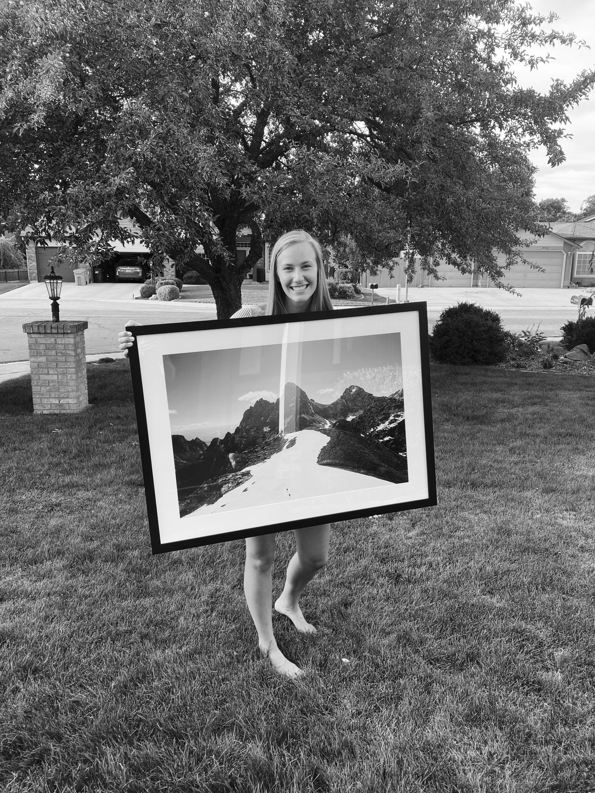 woman holding large framed photo of mountains