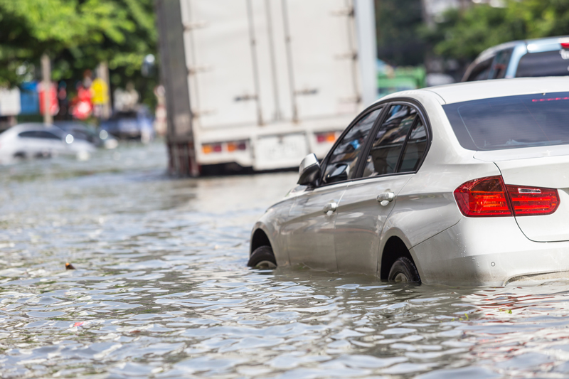Car on a flooded street showing the importance of green roof specifications