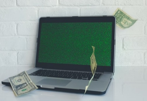 Dollar bills Flying in Front of Laptop