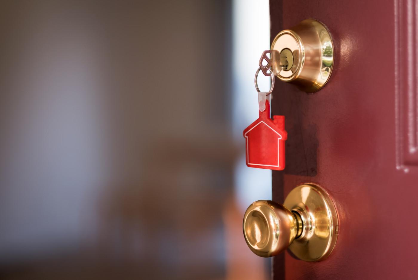 keys hanging in door lock with house keychain