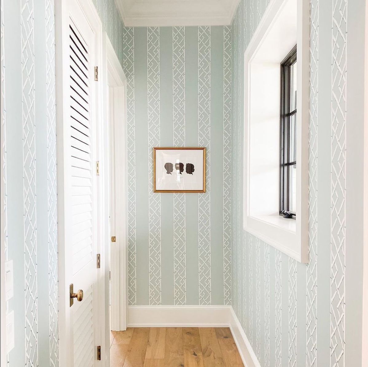 hallway with patterned wallpaper and small picture framed in gold frame
