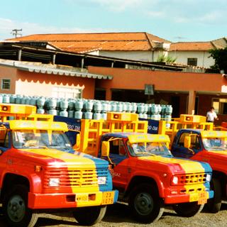 Foto de 3 caminhões da ultragaz estacionados um ao lado do outro, nas cores azul, amarela e vermelha carregados de botijões azuis. No fundo uma casa com paredes na cor terra e um céu azul mais claro, porém com muita luz.