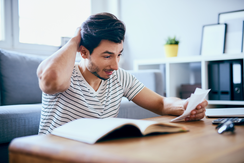 man scratching head looking at paperwork