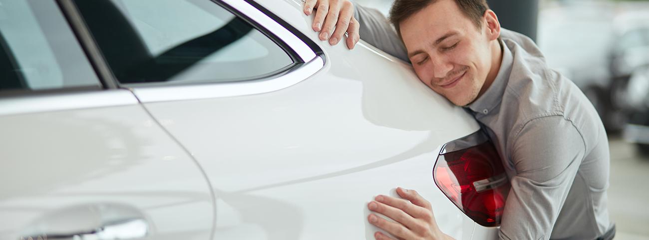 Hombre abrazando auto blanco
