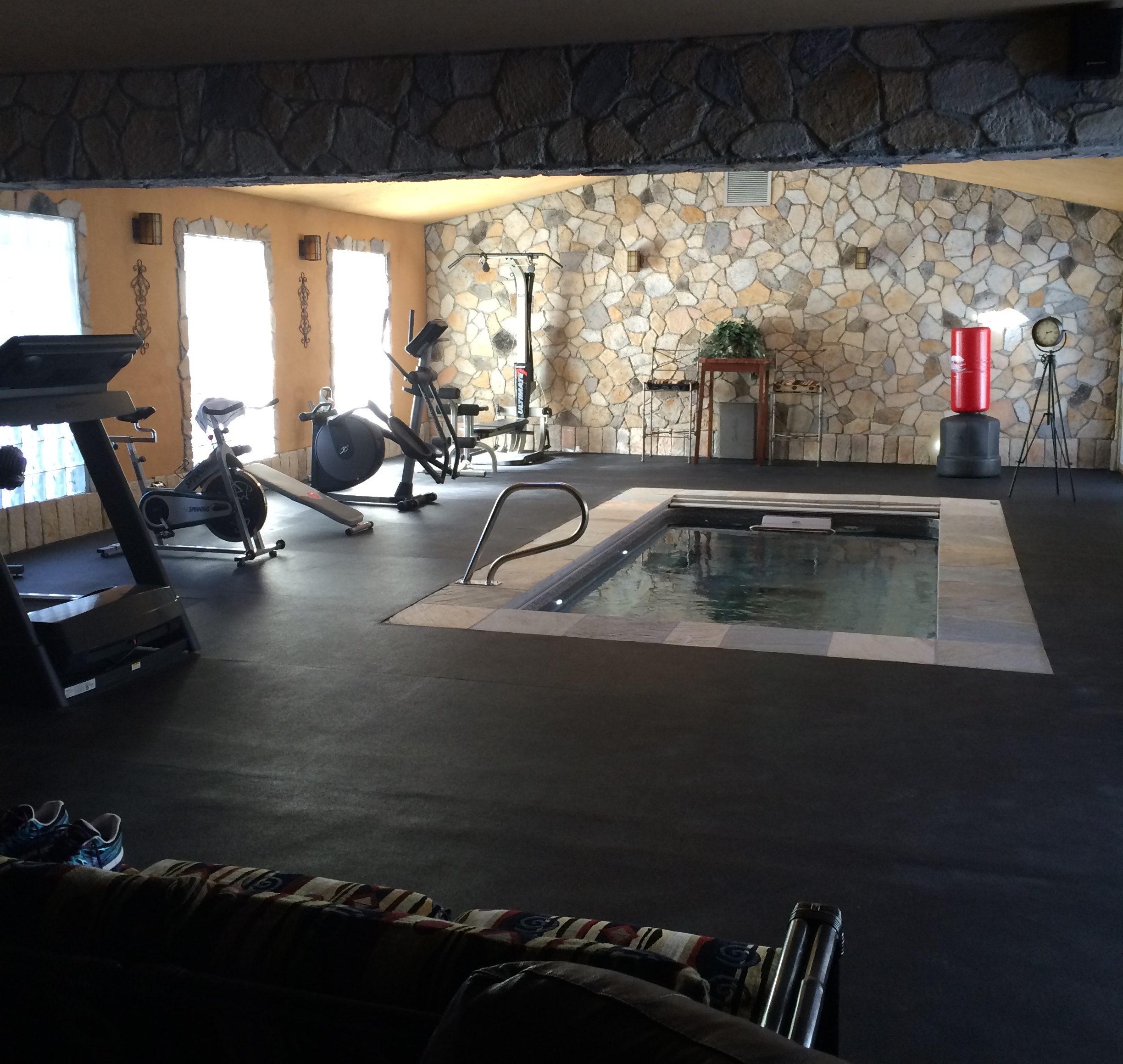 an indoor, fully inground Endless Pools swimming machine in a home gym