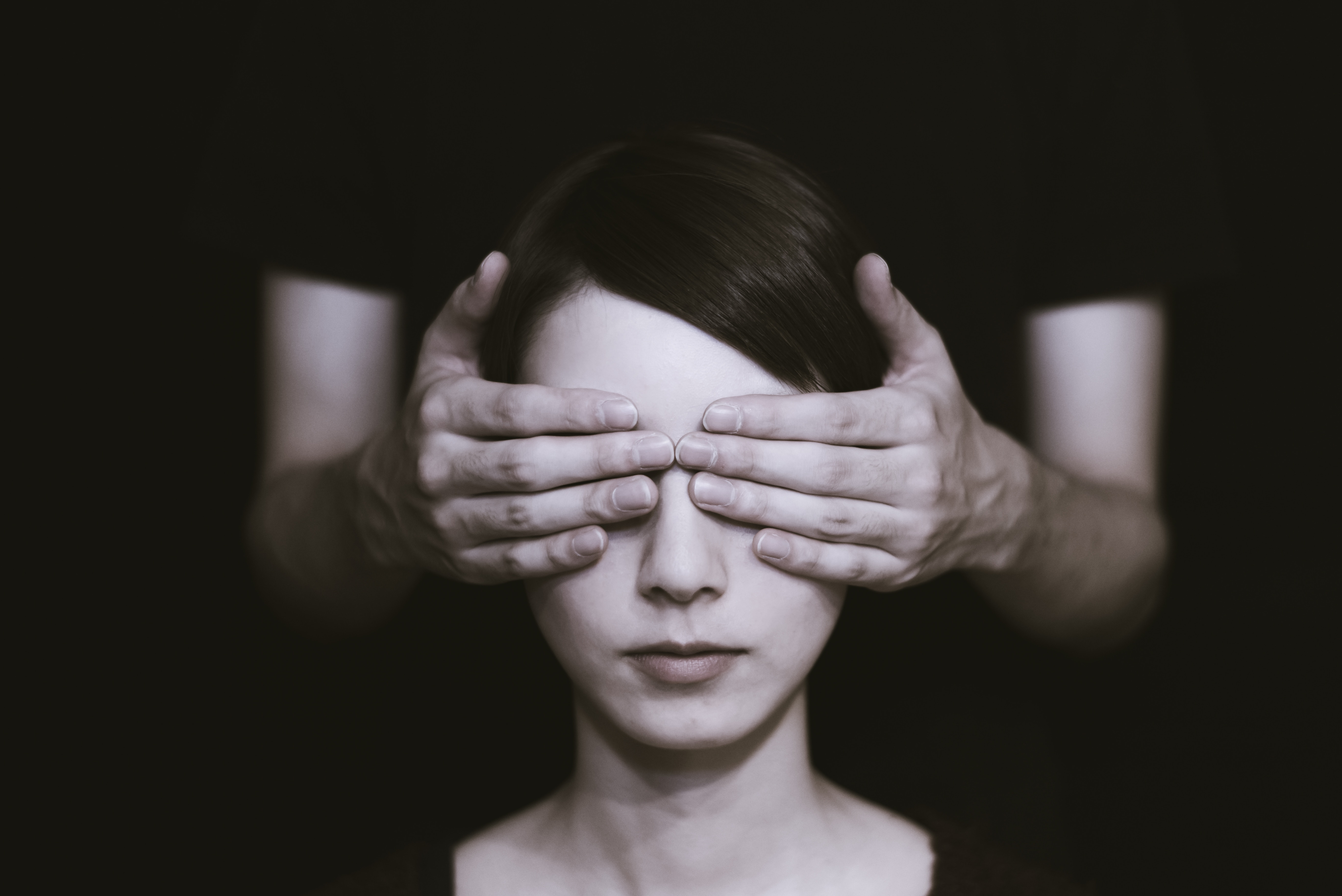 black and white photo of a woman whose eyes are being covering by someone's hands standing behind her