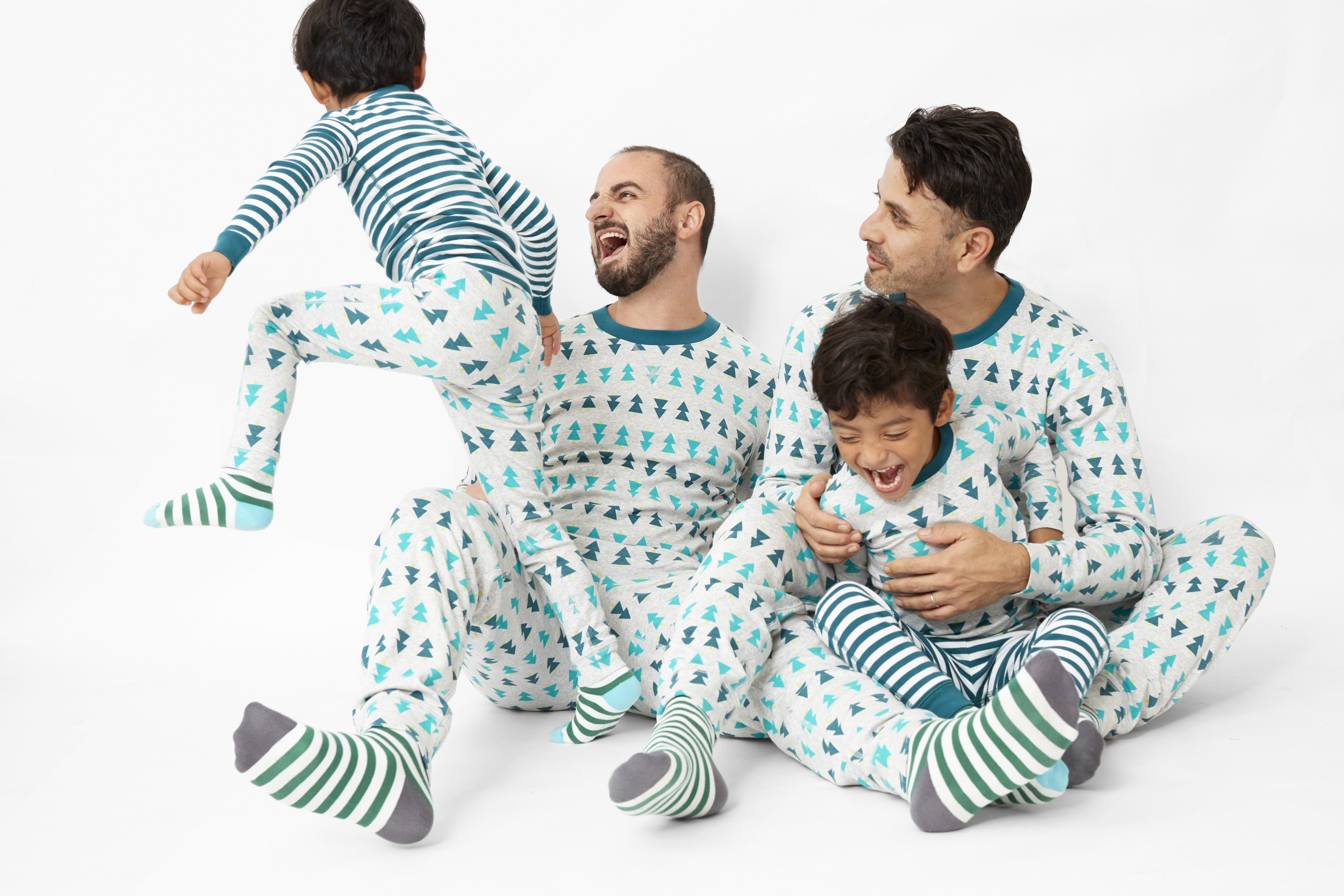 two dads and twin boys wearing tree pajamas