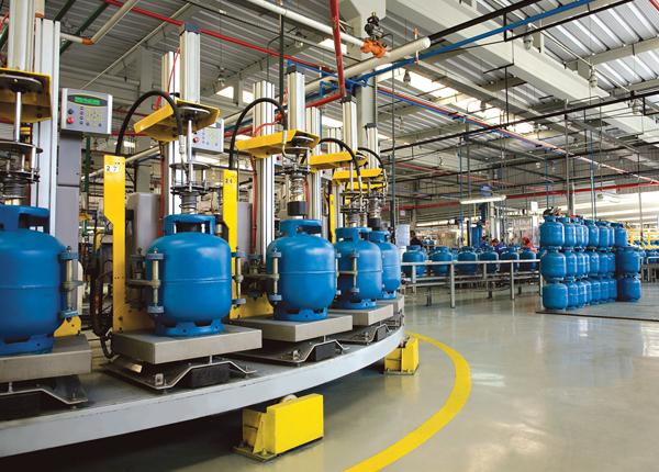 Foto da linha de produção do envasamento dos botijões de 13 quilos. Estão todos enfileirados, são azuis em um ambiente fabril.