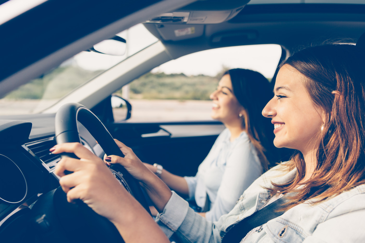 two girls smiling at road while driving