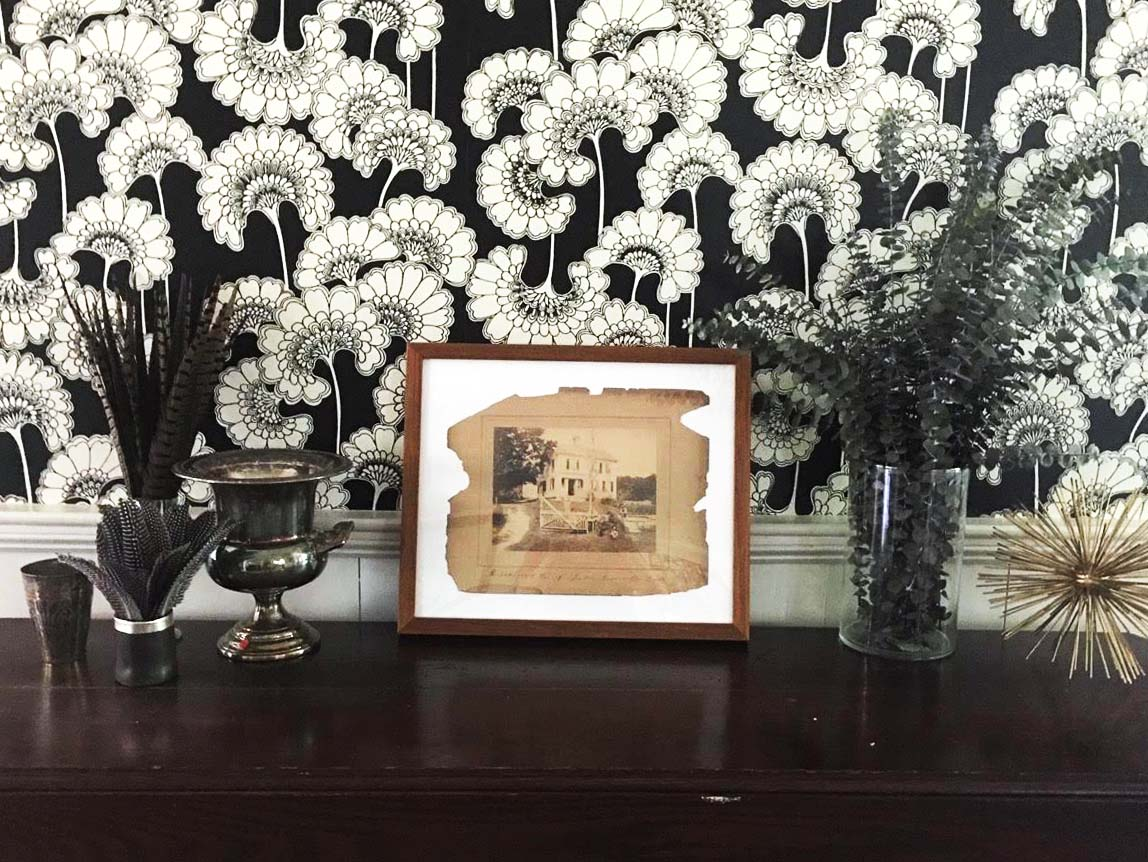 framed photograph on dark wood table against black and white patterned wallpaper