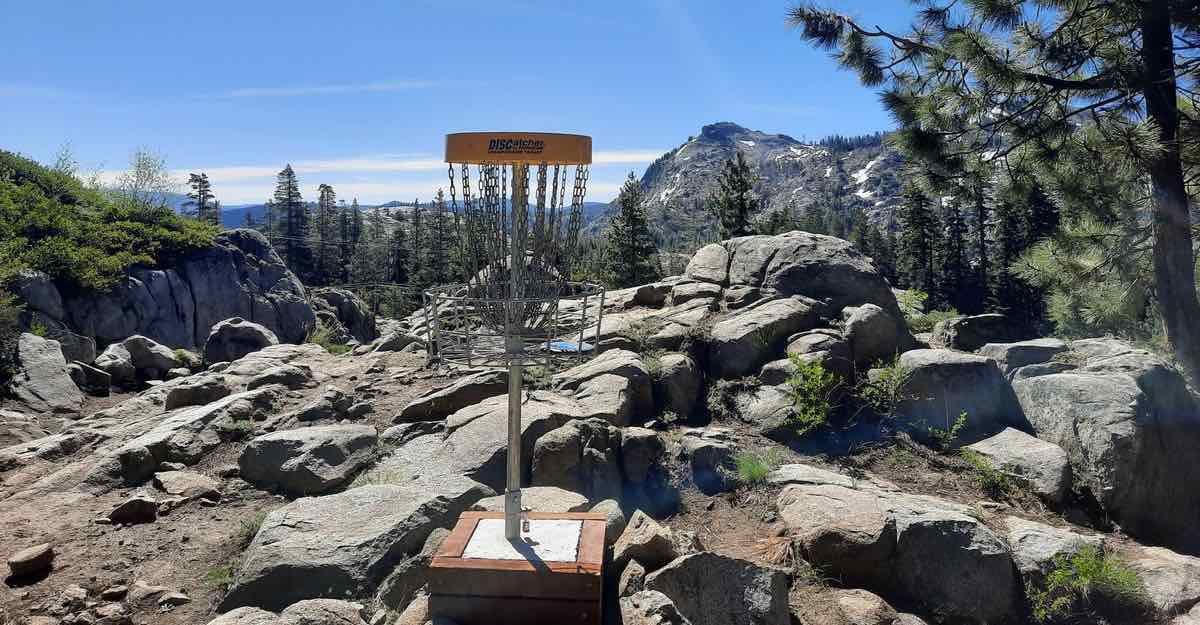 A disc golf basket among rocks in Truckee, CA with Sierra Nevada mountains behind.