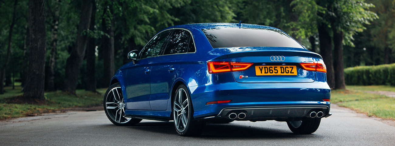Audi S3 azul en medio de la carretera rodeado de arboles