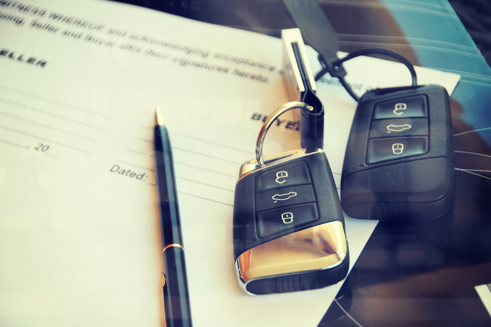 two sets of car keys and a contract