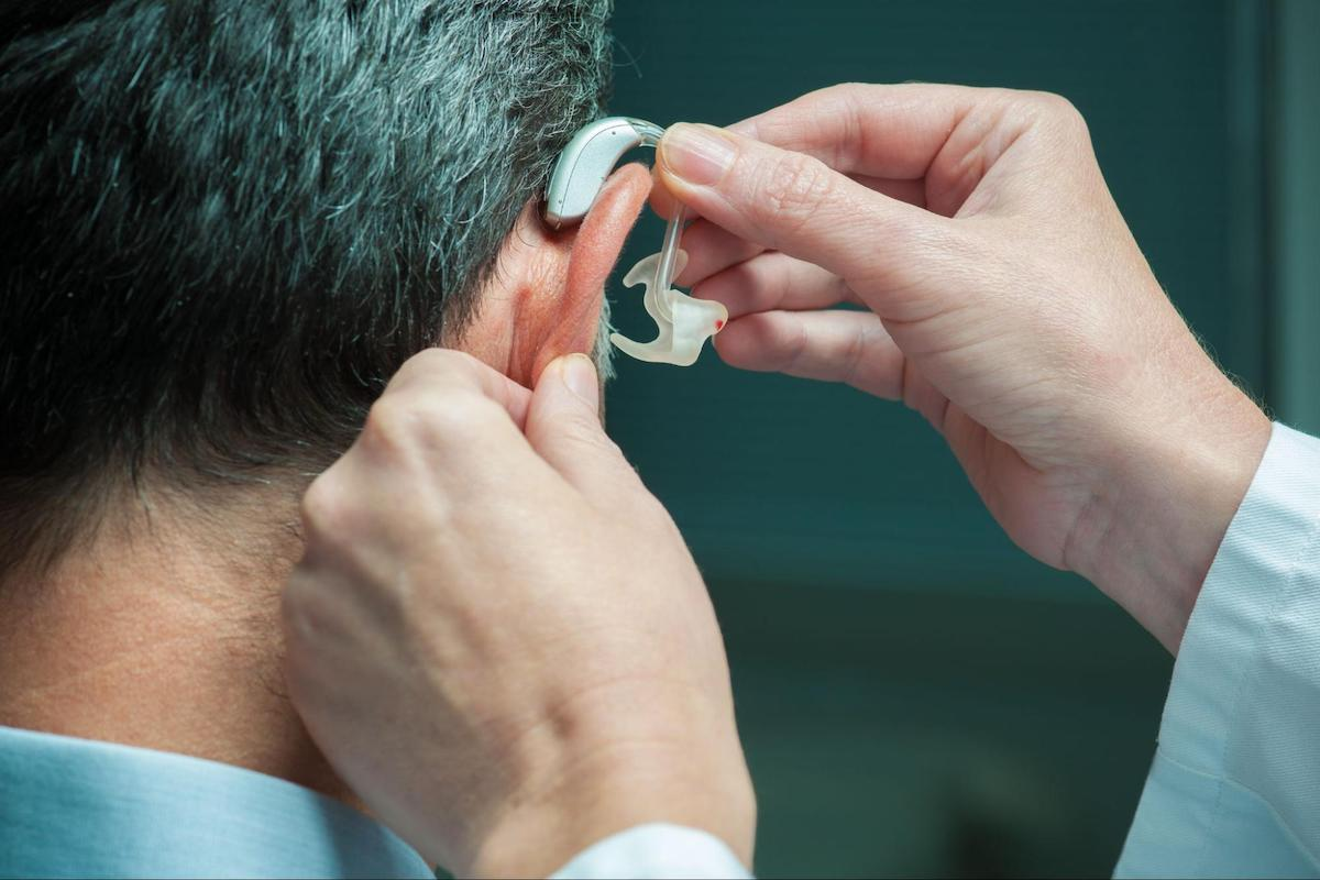 Doctor assisting a male patient in wearing a hearing aid