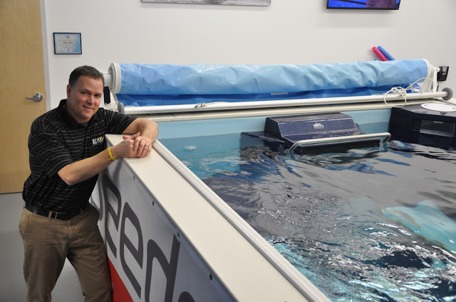 Swim Coach Dean Hutchinson in front of the Endless Pools swimming machine at Strive Physical Therapy