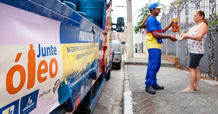 """Foto de um caminhão da ultragaz com uma faixa lateral escrito """"Junte Óleo"""", estacionado em frente à uma residência onde estão na calçada um funcionário ultragaz, vestindo uniforme azul, amarelo e vermelho pegando um pote de óleo das mãos da moradora da casa."""