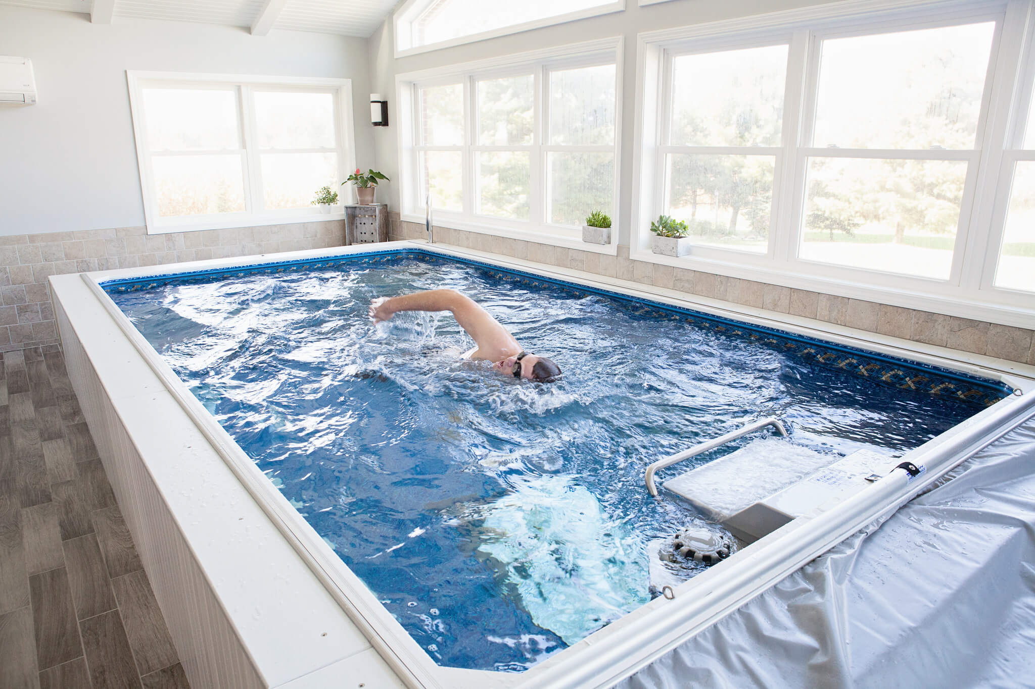 a swimmer swimming in a partially inground Original Endless Pool installed in a sunroom