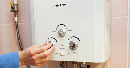 Foto de um aquecedor a gás, branco pregado em uma parede rosa sendo manuseado por uma mão masculina, que ajusta o botão de temperatura.