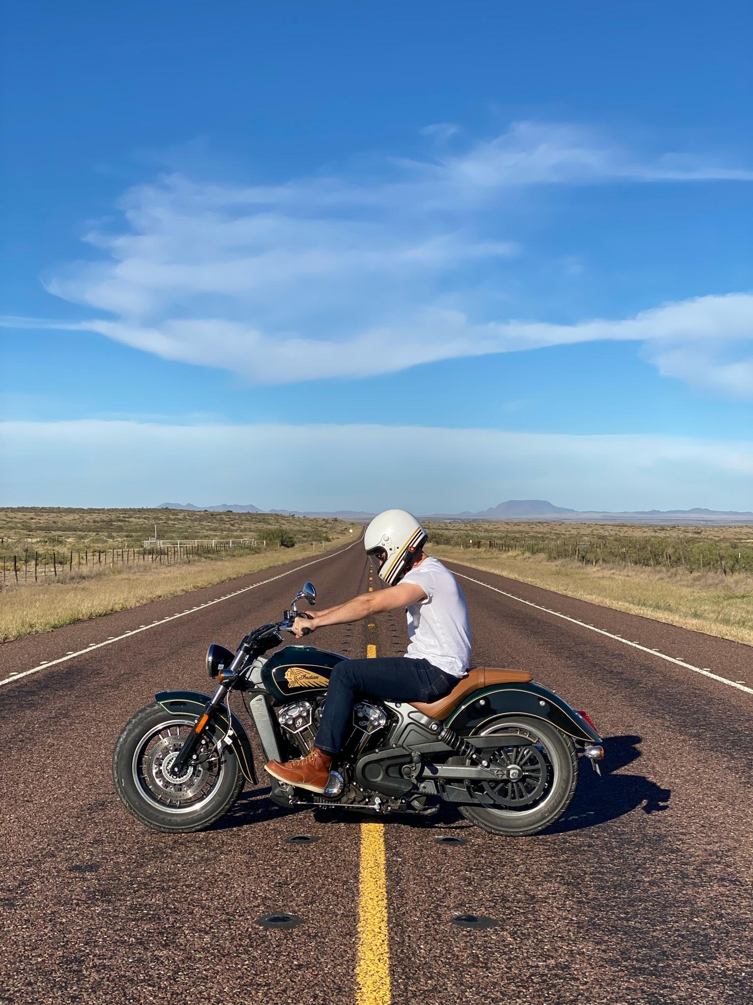 photo of man on motorcycle on highway in Texas desert